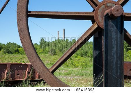 Pair of decaying smokestacks seen through section of a large rusty industrial wheel. Selective focus on the wheel. Lots of texture and grit.