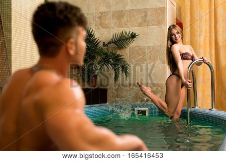 Sexy beautiful long haired blonde in bikini posing in a swimming pool with young man in sauna with luxurious interior
