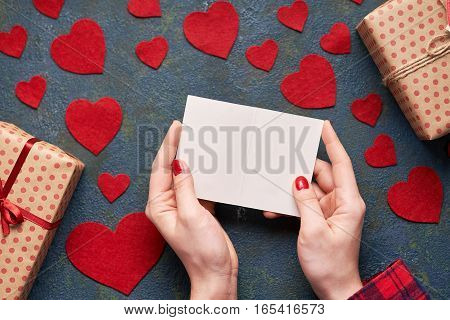 Female hands holding a Valentine card. Background with hearts and gifts on Valentines Day. The concept of a romantic Valentine's Day. Flat lay. Top view table.