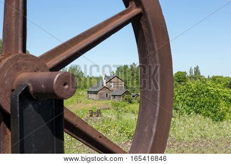 Old abandoned house viewed through a section of a rusty wheel. Selective focus on the house. Part of an abandoned copper mine that is now a Historic National Park in Upper Michigan.