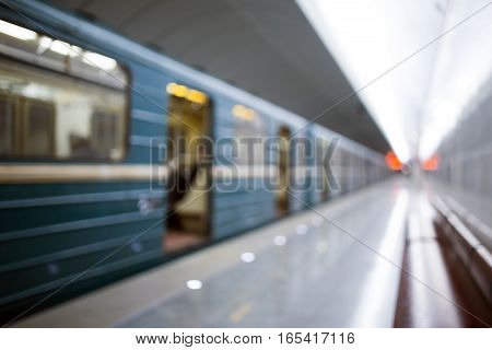 Defocused photo of subway with moving train in tunnel