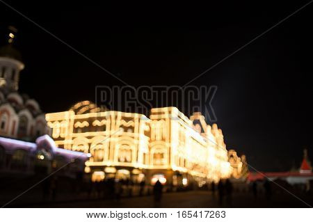 Festive city with festoons glowing at night, blurred photo