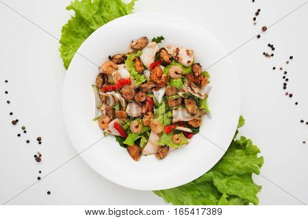 Assorted grilled seafood salad on plate flat lay. Top view on warm side dish with roasted shrimps, mussels and lettuce leaves. Mediterranean cuisine, healthy food, restaurant menu concept