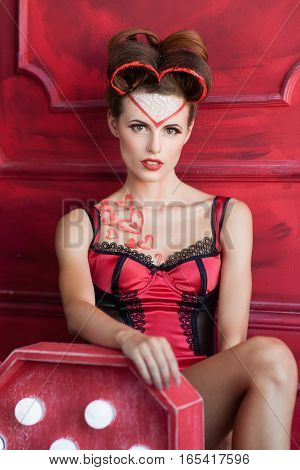 Confident woman seductively looking at camera. Sexy woman in red lingerie posing at chair, free space. Love, temptation, mistress, valentines day concept
