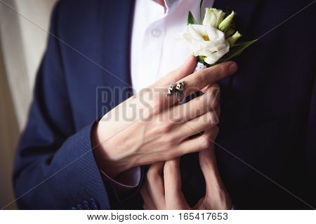 groom boutonniere adjusts his hand in a jacket pocket.
