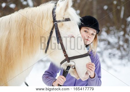 young girl with white horse in winter forest. Equestrian sport background
