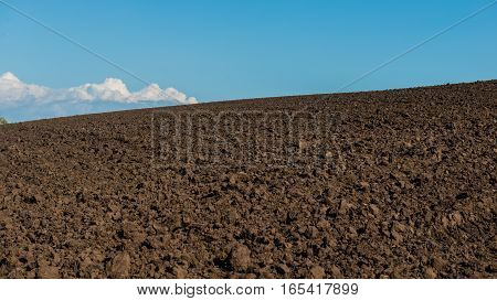 agricultural plowed field and sky landscape panorama