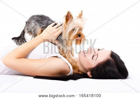 Beautiful young woman, lying with a cute dog breed Yorkshire Terrier, isolated on a white background