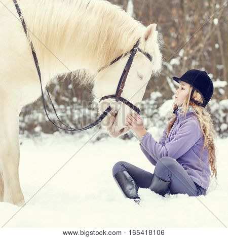 Young teenage girl holding hands to white horse in winter park
