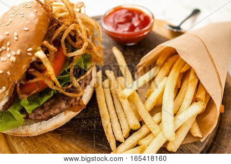 Fresh homemade hamburger with french fries potatoes in bakery paper, served with ketchup sauce. American traditional cuisine, junk fast food, lunch time concept