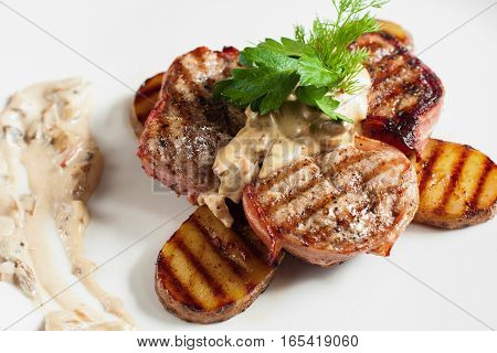 Grilled pork shops with potato on white plate. Barbecue steak served with vegetable and sour mushroom sauce. Meat meal, restaurant menu, junk food concept
