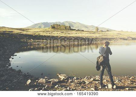 male photographer near lake on sunset background