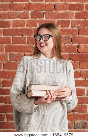 Beautiful laughing student girl portrait. Attractive young woman with books laughing at funny joke. Joy, fun, positivity, good mood concept