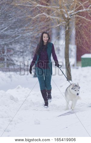 Pretty Smiling Woman Walking with Her Dog Outside. Vertical Image Composition