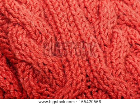 Background of red knitted fabric, texture of knitted wool thread.
