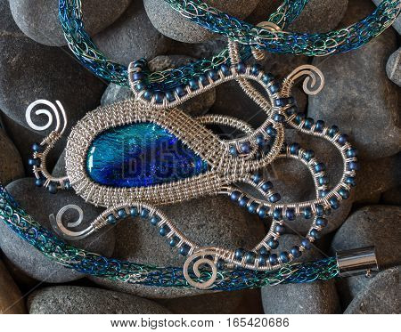 A wire weaved pendant shaped like an octopus grips a viking knit necklace lies on a bed of rocks.