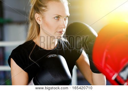 Sportswoman engaged in boxing with trainer in gym