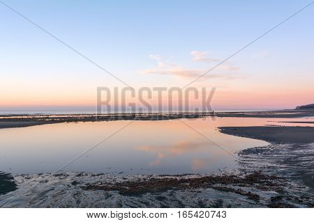 Pre dawn light is reflected in pink on a tidal pool on a Homer Alaska beach.