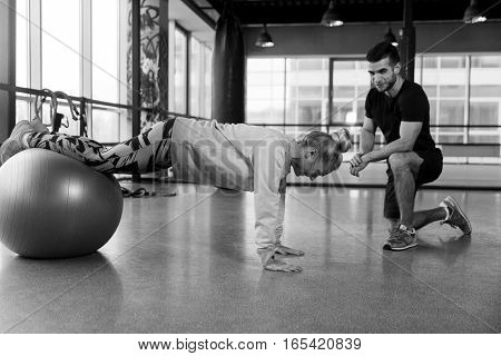 Black- white photo of woman on fitball at gym with trainer
