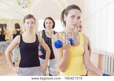 Female Fitness Teamwork Concepts. Closeup of Group of Four Caucasian Female Athletes Exercising with Barbells Indoors. Horizontal Composition