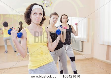 Three Caucasian Females Having a Workout Training with Barbells Indoors. Horizontal Image Orientation