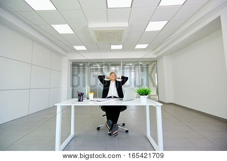 The concept of business winning, luck, dreams, happiness. Businessman in modern office blonde put her hands behind her head.