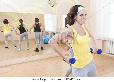 Three Smiling Caucasian Females Having a Workout Training with Barbells Indoors. Horizontal Shot