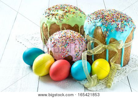 Traditional Easter treats: Easter cakes and colorful easter eggs on a white table