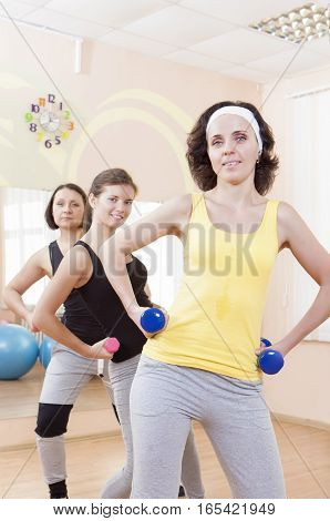 Portrait of Group of Three Caucasian Female Athletes Having a Workout Training with Barbells Indoors. Vertical Image Orientation