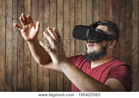 Bearded man with virtual reality glasses showing gesture on the wooden background