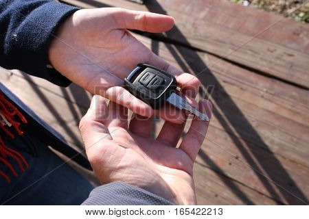 Buyer's hand taking a car key .