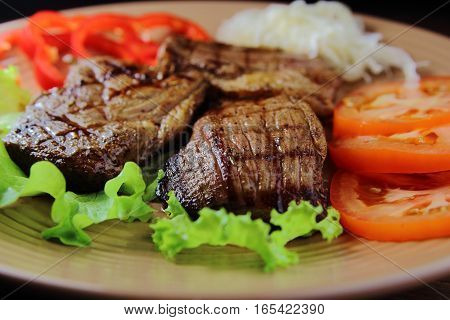 beef steak with fresh vegetables on a lettuce leaf