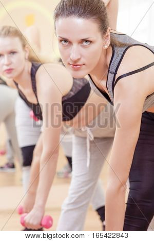 Portrait of Three Nice and Attractive Fitwomen Having a Stretching Workout With Barbelles Indoors Together. Vertical Composition
