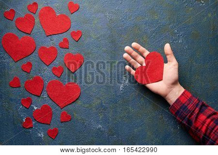 Red Heart Love is in Women's Hand. Concept for Valentine's day. Concrete background with hearts and gifts on Valentines Day. Flat lay. Top view table. Symbol of love.