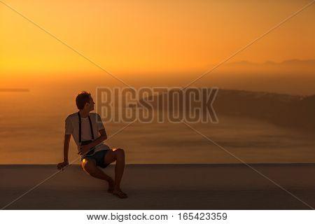 Man sitting on the roof at sunset. Beautiful view on caldera at evening sun. Imerovigli Santorini island Greece