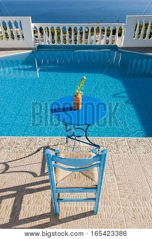 table and chair beside water pool, villa, greece