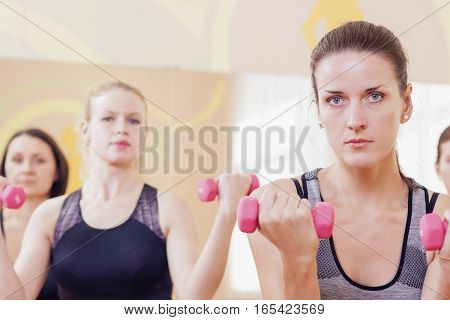 Fitness Concepts. Three Attractive and Positive Caucasian Females Having a Workout Training with Barbells Indoors. Horizontal Image