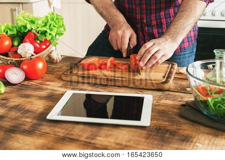 Man looking recipe on digital tablet and cooking healthy food in the home kitchen on a sunny day