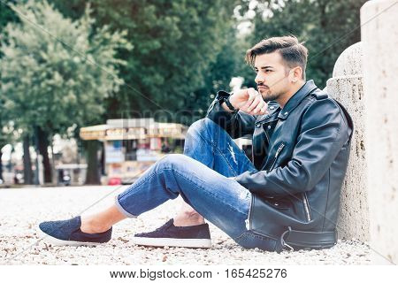 Handsome gorgeous young man outdoors. Casual jeans and leather jacket, trousers with cuffs, rolled up pants.