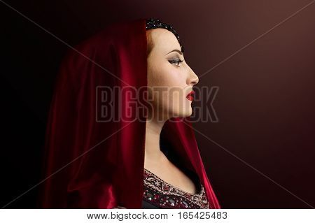 Renaissance woman photo. Beautiful Renaissance woman in a red head scarf profile view portrait photo.