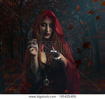 Sorceress in the forest. Beautiful sexy sorceress in red cloak holding antique clock watch standing in the forest photo. poster