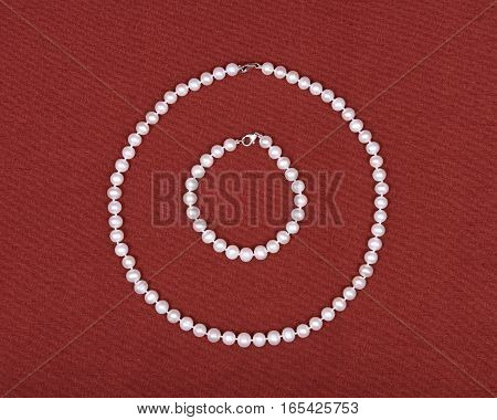 Freshwater pearl necklace on red fabric background