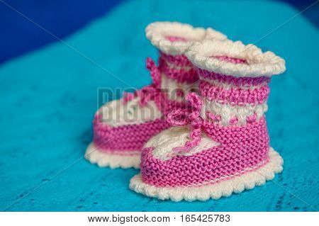 Small white-pink children's knitted booties, hand-knitted, on a wool background