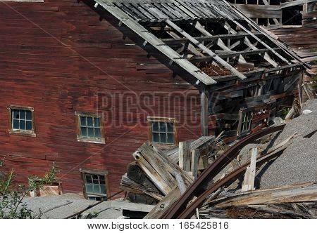 An industrial building at the Kennicott Mine is succoming to the elements with the roof already gone and the walls decaying.