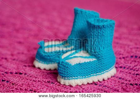 Small white-blue children's knitted booties, hand-knitted, on a wool background