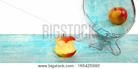 Bit of apple and reflection in a mirror of the whole apple. The taken a bite apple is reflected in a blue colored table as whole. At the left above empty seat white
