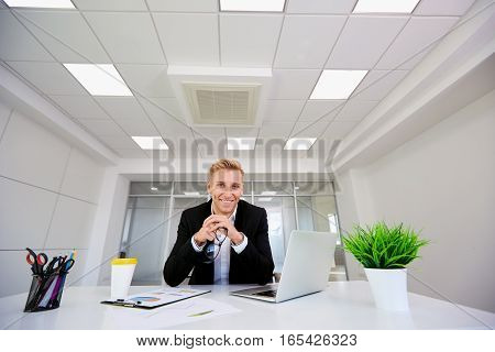 Young blond businesswoman smiling sitting at table with glasses in hands  a modern office.