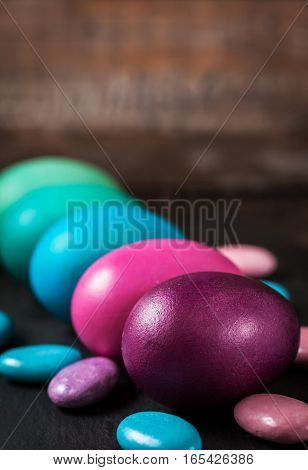 Colorful painted Easter eggs in a carton on dark background