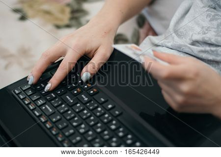 Woman buying online or booking hotel with a laptop and credit card. E commerce concept