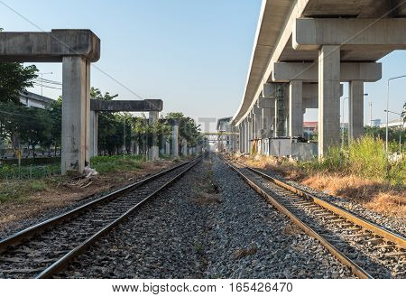 Two railway train under concrete construction blue sky background